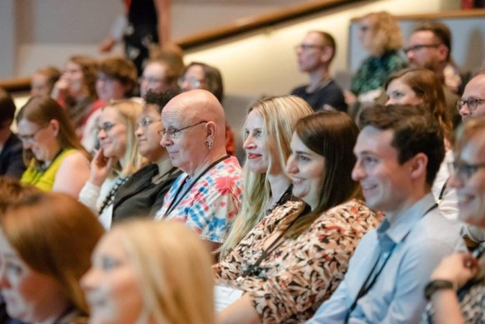 Smiling people sitting in an auditorium